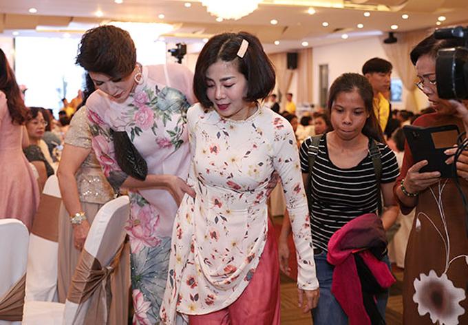 Diễn viên Những thiên thần áo trắng diện áo dài họa tiết hoa. Vì trang phục quá dài nên cô được cựu người mẫu Trang Trần dìu đi chào hỏi mọi người.