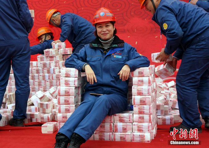 An employee sits on a seat piled up in cash.