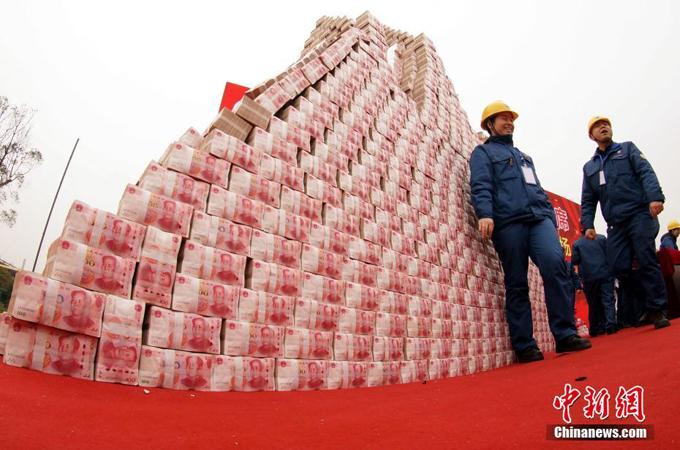 Người đàn ông này tranh thủ tạo dáng bên núi tiền trước khi chúng được phân phát cho các nhân viên trong công ty gang thép Fangda.