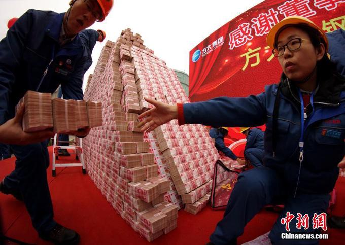 Những cọc tiền mặt được chuyển lên sân khấu. Năm nay, mỗi nhân viên công ty sẽ được thưởng 60.000 tệ (8.800 USD) để đón Tết con Lợn. Số tiền này gấp đôi số tiền thưởng Tết năm ngoái.