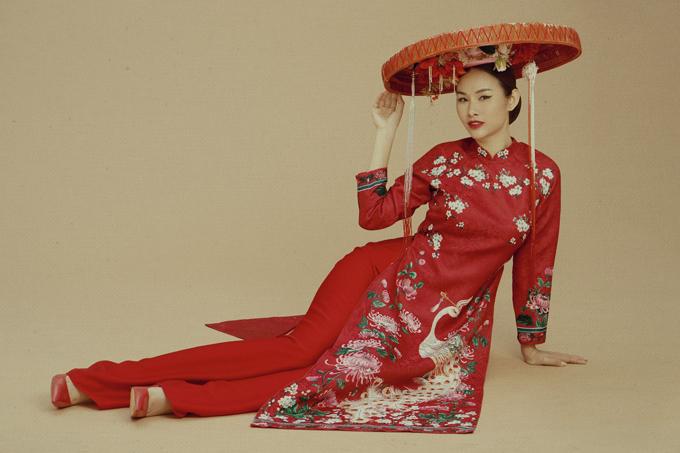 Trang phục gam đỏ in hoa đào, hoa cúc và chim công tượng trưng cho sự may mắn, ấm cúng trong ngày Tết. Chiếc nón quai thao gợi nhớ vẻ đẹp của thiếu nữ Bắc Bộ thời xưa.
