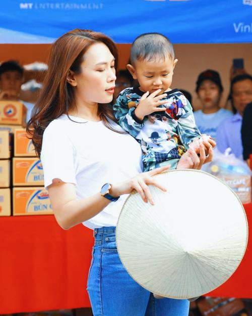 Mỹ Tâm đội nón lá, bế em bé khi đi giao lưu cùng bà con trong chuyến đi từ thiện tại Vĩnh Long.