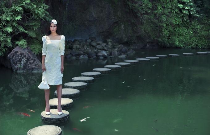 Hoa hậu khoe dáng mảnh mai khi diễn xuất trên một hồ nước.