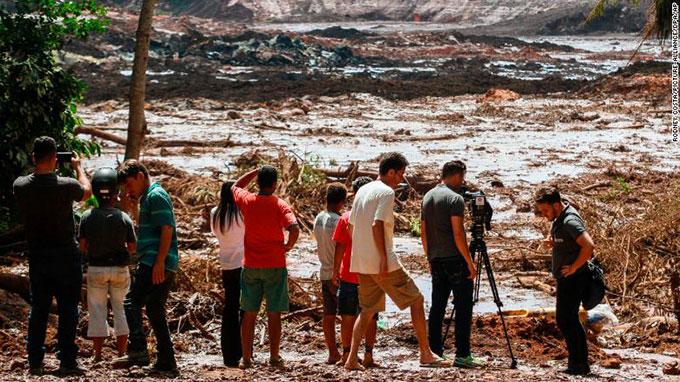 Ngừoi dân Brumadinho, Brazil, thẫn thờ đứng nhìn vùng đất của mình tan hoang sau thảm kịch hôm 25/1. Ảnh: AP.