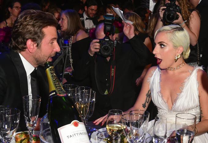 Hai người buôn chuyện rôm rả khi ngồi cùng bàn tiệc. Sau khi hợp tác cùng trong A Star Is Born, Bradley và ngôi sao nhạc pop đã trở thành những người bạn thân thiết. Cả hai từng cống hiến hết mình cho bộ phim và ngưỡng mộ tài năng của đối phương. Gaga đã rất ngỡ ngàng trước giọng hát của Bradley còn tài tử Hollywood lại thán phục khả năng diễn xuất của nữ ca sĩ 32 tuổi.