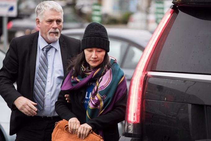 Nhân viên an ninh đi cùng giám đốc Huawei (phải) tại Vancouver sau khi bà được tại ngoại. Ảnh: JWS.