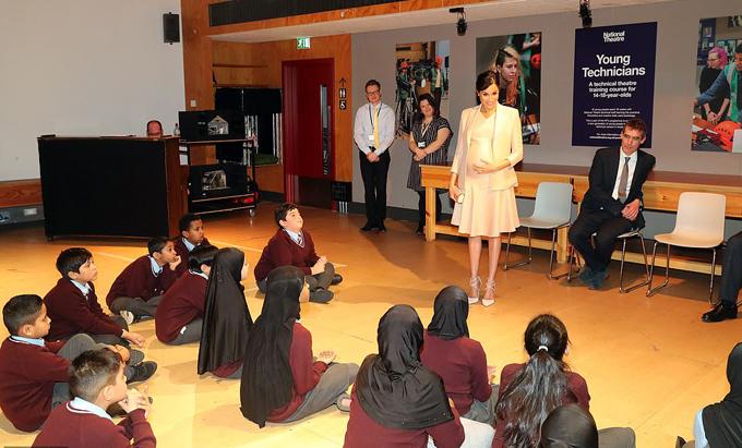 Nữ công tước xứ Sussex trò chuyện với nhóm học sinh tiểu học biểu diễn tại Nhà hát Quốc gia London hôm 30/1. Ảnh: PA.