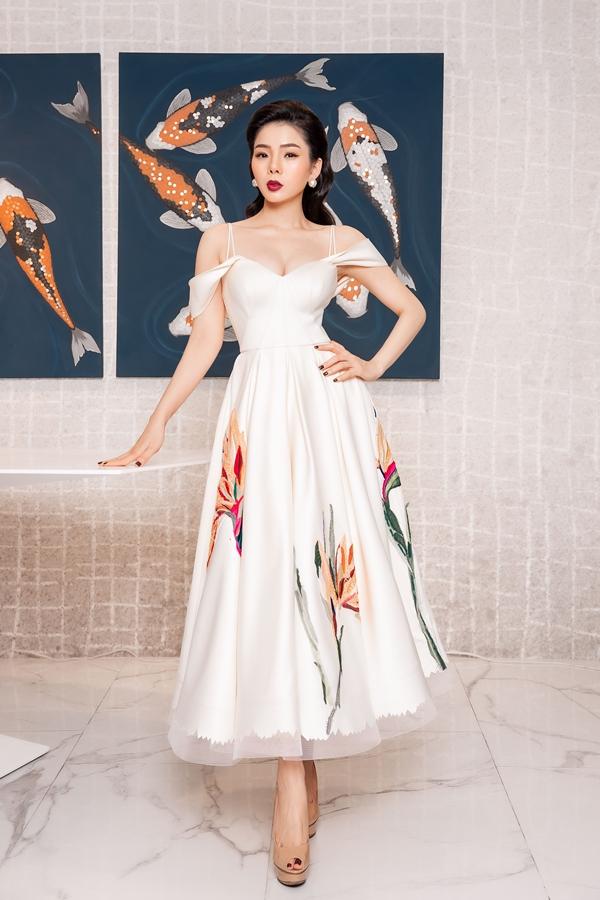 Giọng ca Duyên phận khoe ngực đầy và vóc dáng thon thả với váy trễ vai cầu kỳ. Họa tiết hoa lá đính kết tỉ mỉ và hài hòa trên nền vải trắng, tạo điểm nhấn cho chiếc váy.