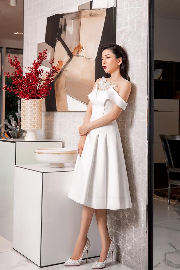 Phần cổ cách điệu với hoa ren thêu nổi và những đường xếp nếp nơi tùng váy giúp trang phục thêm thu hút.