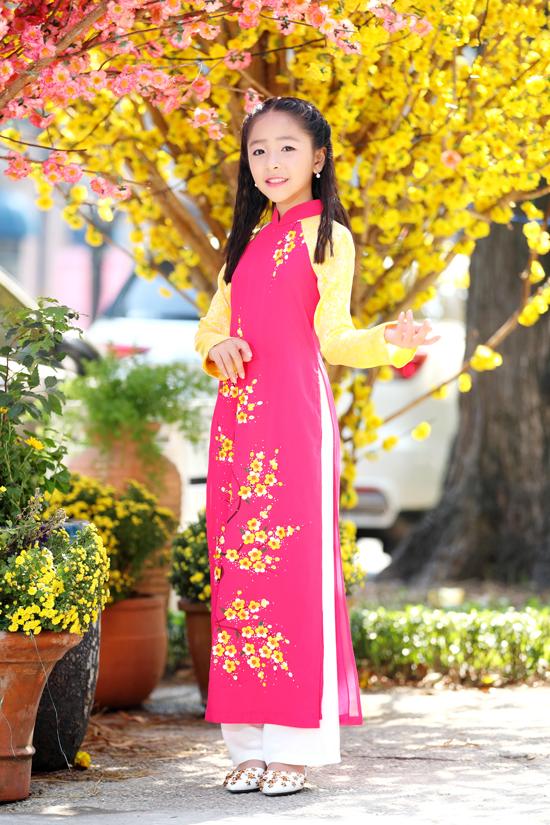 Bé Như Y duyên dáng cùng trang phục áo dài cách tân hòa trộn sắc vàng tươi của nắng và tông hồng đậm cánh đào.