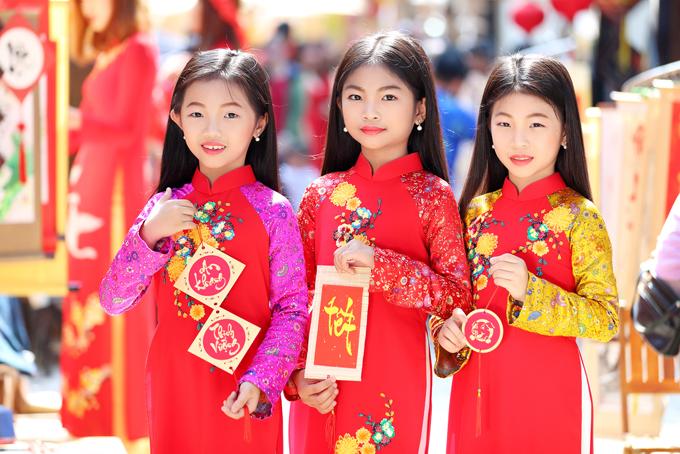 Chị em sinh 3 Tam Bảo cùng diện áo dài đỏ tươi trang trí hoa cúc vàng và cầm những lời chúc mừng năm mới an khang thịnh vượng, phát lộc - phát tài.