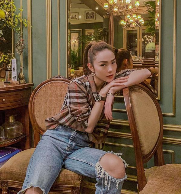 Minh Hằng trẻ trung cùng quần jeans rách bụi phủi và sơ mi burberry họa tiết kẻ nova. Đồng hồHublot và trang sức từ Cartier được mix một cách hài hòa về màu sắc để giúp người đẹp hoàn thiện set đồ.