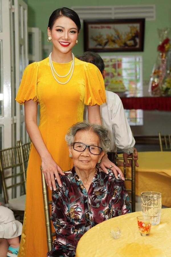Hoa hậu Trái đất 2018 Phương Khánh hoá quý cô cổ điển khi về quê nhà Bến Tre dự tiệc tất niên cùng gia đình chiều 1/2. Cô chụp hình cùng bà ngoại.