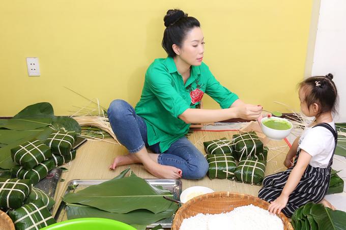 Vừa gói bánh nữ diễn viên vừa tranh thủ chăm sóc, đút cho con gái út ăn.