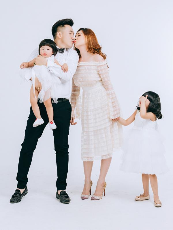 Bé Shu ngượng ngùng che mắt khi bố mẹ âu yếm hôn nhau trong lúc chụp ảnh.