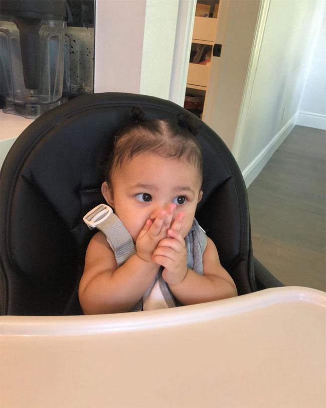 Cô bé như búp bê bên bàn ăn.