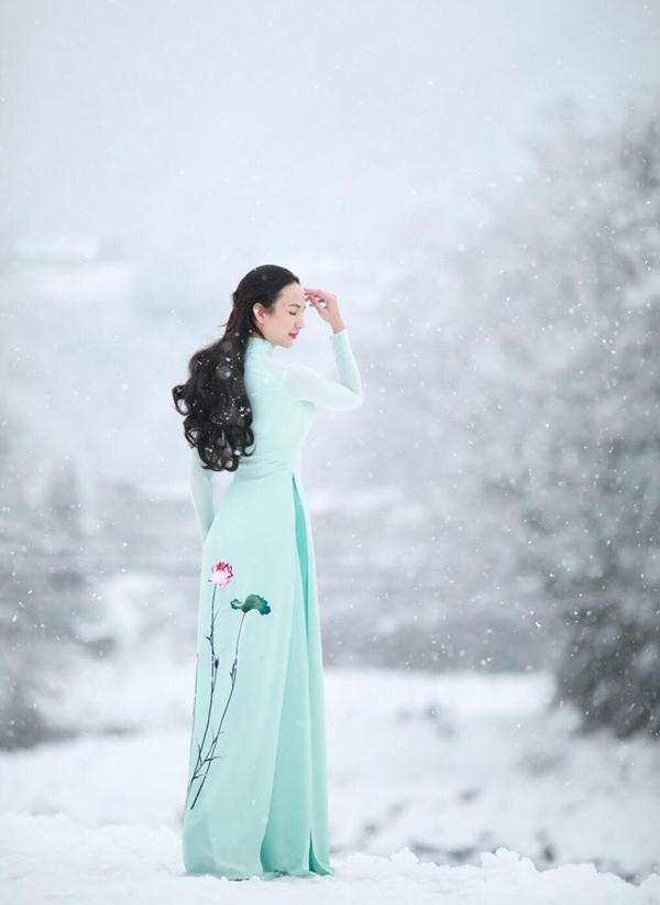 Người đẹp chịu cái lạnh buốt da để thực hiện bộ ảnh mặc áo dài họa tiết hoa sen tạo dáng giữa trời tuyết.