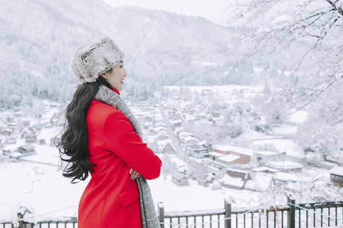 Diện áo khoác đỏ, Hoa hậu Du lịch 2008 nổi bật giữa khung cảnh thiên nhiên chỉ toàn màu trắng.