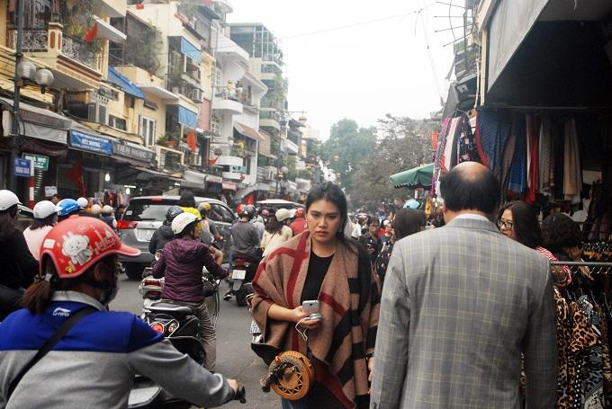 Người đi bộ phố cổ Hà Nội lạc lối trong chiều 29Tết do dòng xe cộ đổ về các khu phố lớn, vừa đi chơi vừa tranh thủ nhặt đồ xả hết ăn Tết bày la liệt trên vỉa hè.