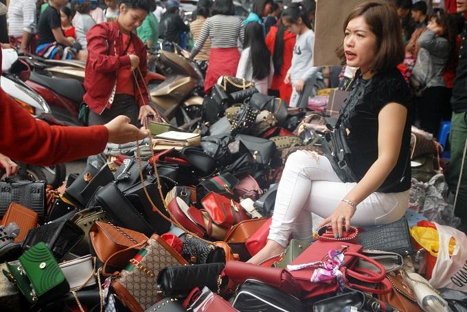 Một phụ nữ bán túi xách 120.000-150.000 đồng tại Hàng Đàoliên tục bị chị em quây và phải không ngớt từ chối bán giá thấp hơn.