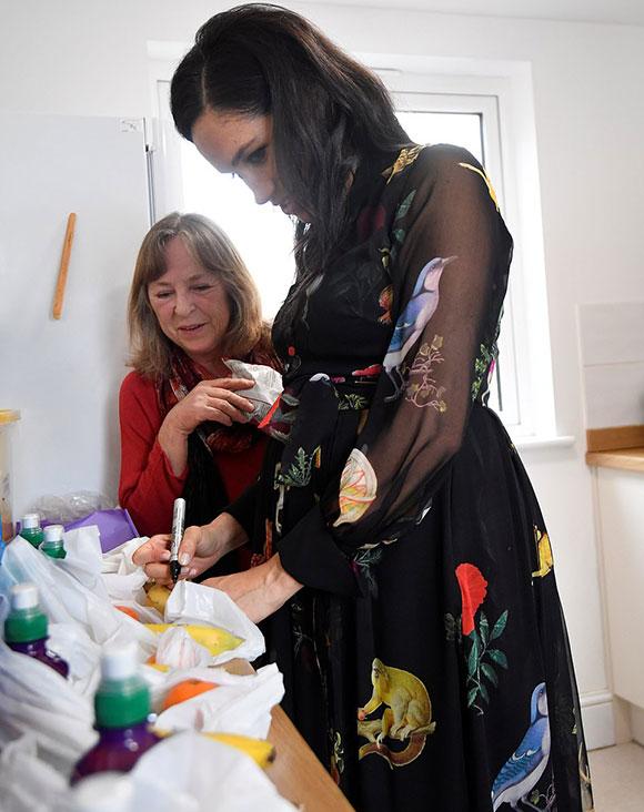 Sau khi tuyên bố mình phụ trách chia trái cây vào các gói đồ, Meghan đã lấy bút để viết những câu khích lệ như Bạn thật đặc biệt, Bạn rất dũng cảm, Bạn đáng được yêu và Bạn thật mạnh mẽ lên vỏ của từng quả chuối. Ảnh:Reuters.