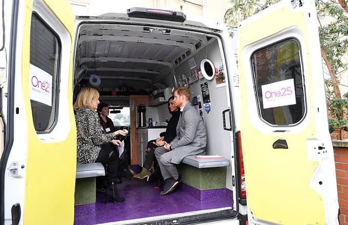 Vợ chồng Harry - Meghan ngồi lên một trong những chiếc xe tải phân phát đồ ở khu phố đèn đỏ Bristol. Những chiếc xe này thường di chuyển 5 đêm mỗi tuần để cung cấp thức ăn, quần áo ấm, bao cao su và những lời khuyên cho các phụ nữ đứng đường.