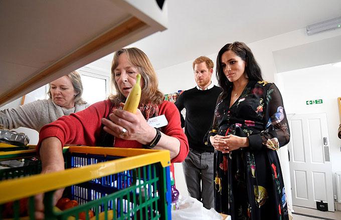 Trong khi vào bếp hỗ trợ nhân viên của tổ chức sắp những gói đồ ăn để trao tặng các phụ nữ trong khu phố đè đỏ, Meghan đã nảy ra sáng kiến viết thông điệp lên các quả chuối nhằm ghi dấu ấn riêng của bản thân. Ảnh:Reuters.