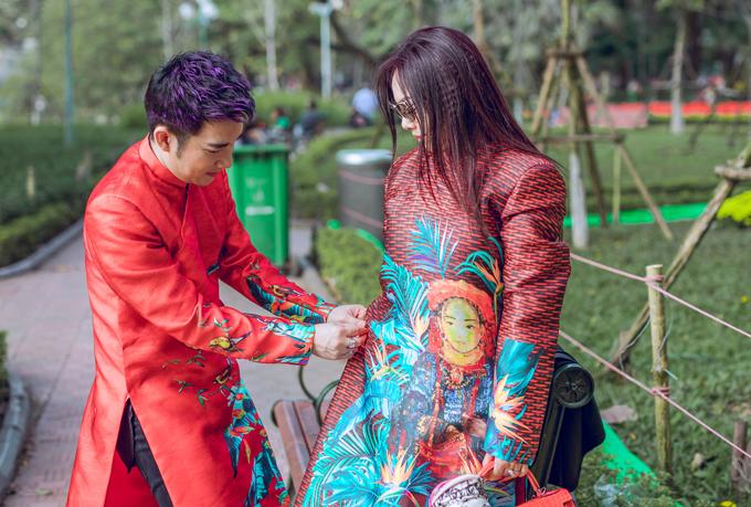 Chị kết nghĩa ngẫu hứng muốn mặc bộ áo dài của Quang Hà để chụp cùng anh một tấm ảnh kỷ niệm với trang phục truyền thống tại quê hương. Do bộ đồ khá rộng với phụ nữ nên người chị có thể mặc trùm lên trang phục của mình. Quang Hà ân cần chỉnh sửa áo dài cho chị.