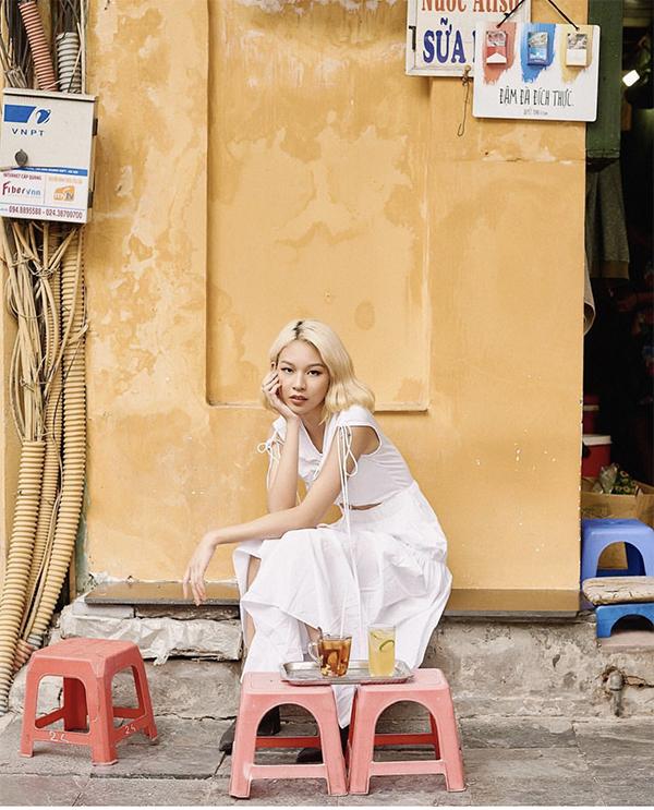 Với mục đích tôn mái tóc vàng mới nhuộn để đón Tết, Phí Phương Anh đã chọn mẫu váy trắng trang trí dây rút bắt mắt. Trang phục đi chơi xuân của cô khác hẳn sự nổi loạn và phá cách thường ngày.