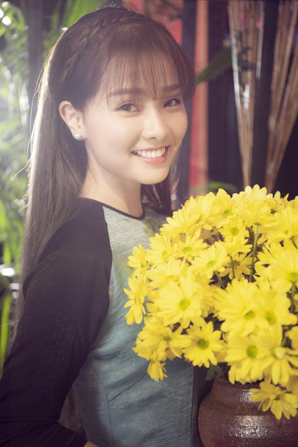 Người đẹp phim Tôi thấy hoa vàng trên cỏ xanh rạng rỡ bên bình hoa cúc ngày Tết.