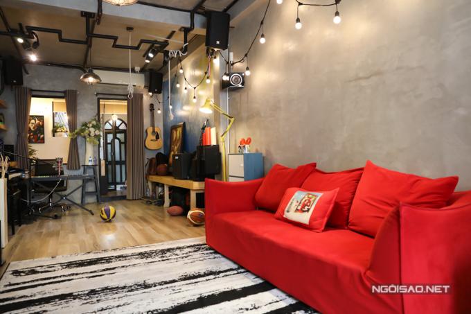 Chiếc ghế sofa màu đỏ tạo điểm nhấn nổi bật cho ngôi nhà.