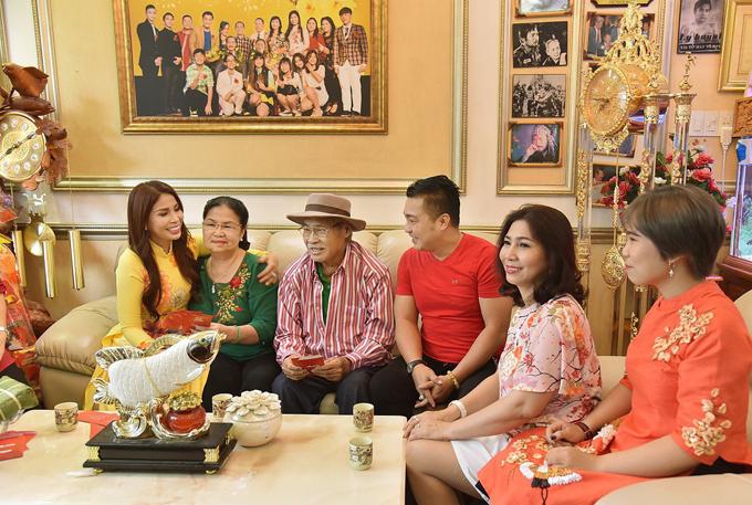 Lý Hương quây quần ăn Tết cùng bố mẹ, anh trai Lý Hùng (áo đỏ) và các chị gái. Cô đưa hình ảnh sum vầy, ấm cúng này vào MV mới.