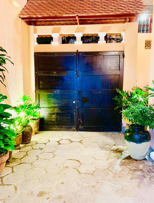 Khung cửa gỗ và khoảng sân rợp bóng cây xanh mở ra hai không gian hoàn toàn đối lập: phía trong là nhà của Thúy Nga ấm áp, yên bình, còn bên ngoài là phố thị ồn ào, tấp nập.