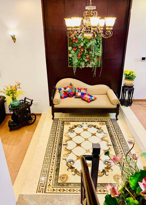 Khu vực tiếp giáp giữa phòng khách và phòng ăn, Thúy Nga kê một chiếc ghế sofa dài và trải thảm tông nâu - trắng kem chủ đạo. Cách kết hợp màu sắc này khiến cho ngôi nhà dù mang hơi hướng cổ điển những không bị già nua, nặng nề. Phía trên tường, chị treo một bức tranh 3D hoa sen đá - loài cây chị yêu thích và cũng trồng rất nhiều trong ngôi nhà bên Mỹ.