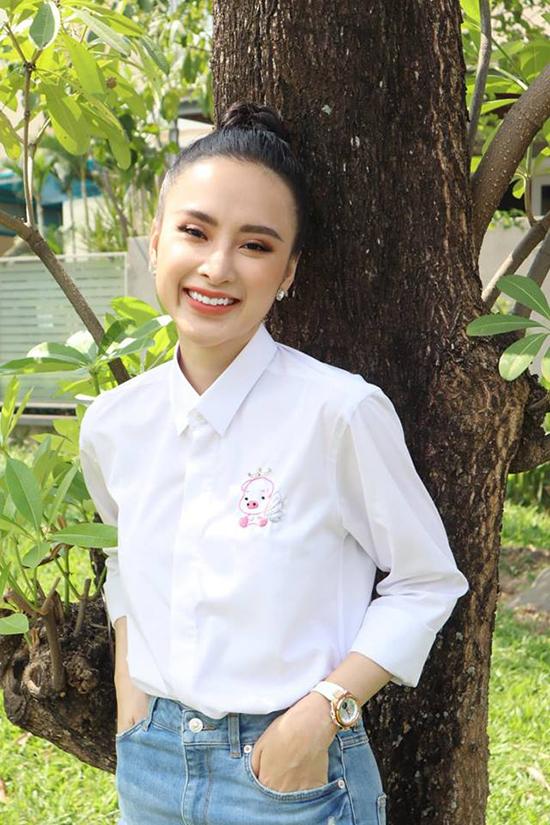 Được mệnh danh là một trong những nữ hoàng thảm đỏ nổi bật của showbiz Việt, nhưng khi tham gia các hoạt động từ thiện, cộng đồng, Angela Phương Trinh lại chọn trang phục rất đơn giản. Áo sơ mi trắng, trang tí họa tiết chú heo hồng được người đẹp phối cùng quần jeans trẻ trung.