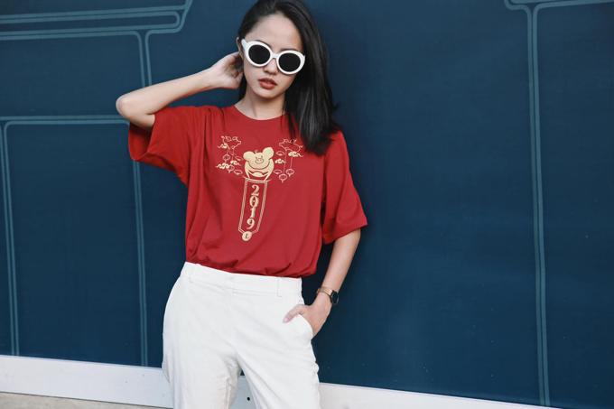 Người mẫu Thanh Vy chọn áo thun tông màu đỏ tươi đến từ thương hiệu trong nước để mix đồ dạo phố. Phối cùng mẫu áo có họa tiết hợp mốt là sự đồng điệu của quần âu và kính mát tông trắng.
