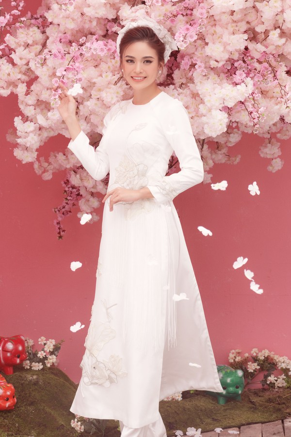 Á hậu mâu Thủy nền nã với áo dài trắng tinh khôi. Kiểu áo tưởng chừng như đơn giản với thiết kế cổ tròn, dáng suông nhưng họa tiết lại được tô điểm cầu kỳ bằng nhiều cánh hoa xếp khối 3D.