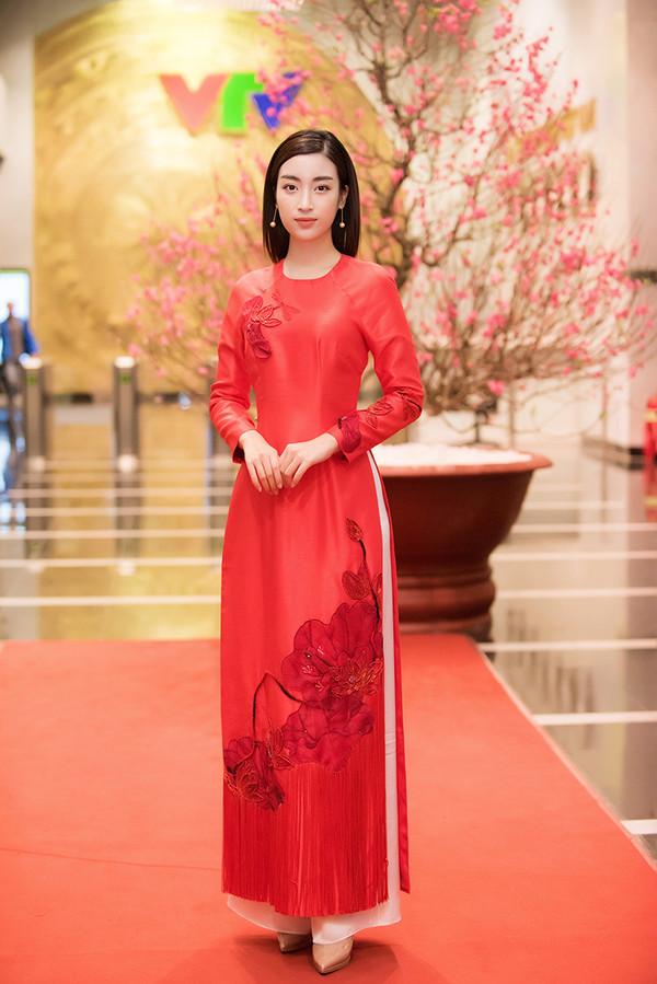 Đỗ Mỹ Linh chọn áo dài đỏ thắm khi đi ghi hình cho chương trình Cặp lá yêu thương. Mẫu áo dài cách tân của người đẹp được trang trí họa tiết hoa sen kiểu cách cùng tua rua đi kèm.