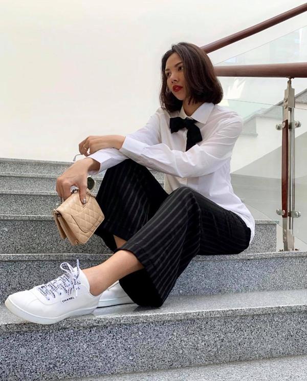 Sơ mi trắng đi kèm nơ tông màu tương phản cũng được Minh Triệu yêu thích. Cô chọn bộ phụ kiện của Chanel để giúp mình tôn nét năng động.