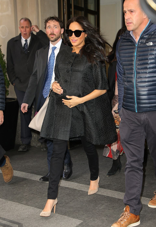 Meghan Markle was seen cradling her baby bump as she left the New York hotel where her baby shower is thought to be taking place, shortly after her guests began arriving