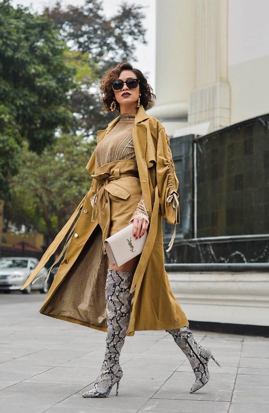 Lấymàu camel làm chủ đạo,Phương Mai kết hợpchân váy ngắncùng áo ánh kim vàtrenchcoat. Đôi boots cao họa tiết da trăn là điểm nhấn giúp cô thêm sành điệu.