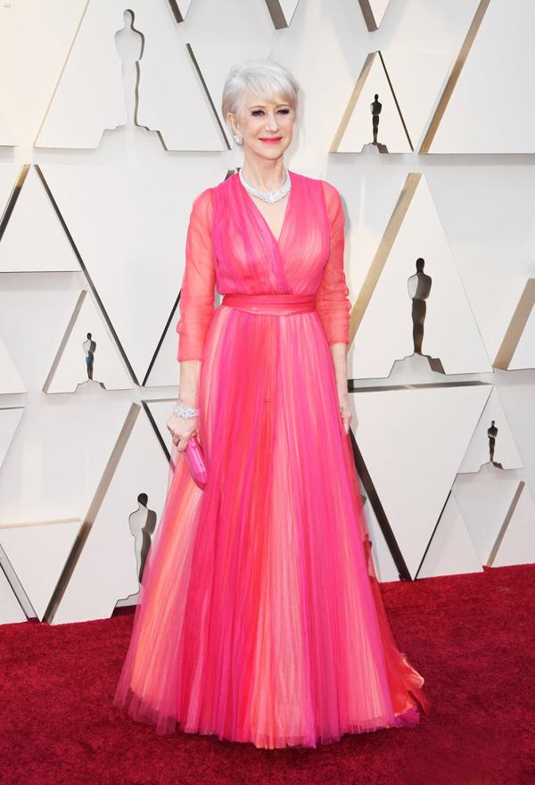 Tối 24/2, Lễ trao giải Oscar lần thứ 91 diễn ra tại Los Angeles, quy tụ sự góp mặt của nhiều nghệ sĩ danh tiếng. Ngôi sao 73 tuổi Helen Mirren nổi bật trên thảm đỏ với thiết kế Schiaparelli Couture bay bổng, kết hợp bộ trang sức kim cương Harry Winston trị giá 6 triệu USD.