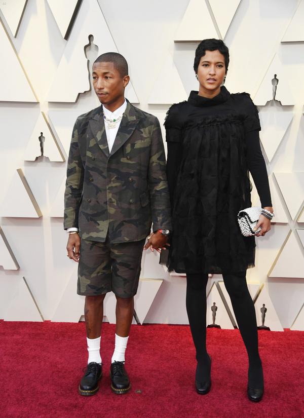 Femail nhận xét Pharrell Williams (trái) trông như một cậu bé ngày đầu tới trường khi diện bộ suit ngắn họa tiết camo.