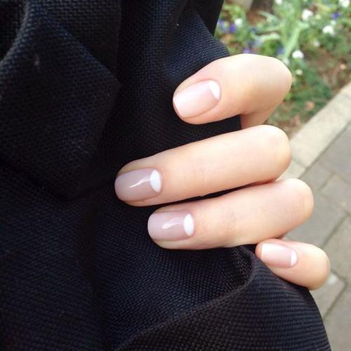 Móng được phủ sơn hồng nude và điểm hình bán nguyệt ở cuối chân móng.