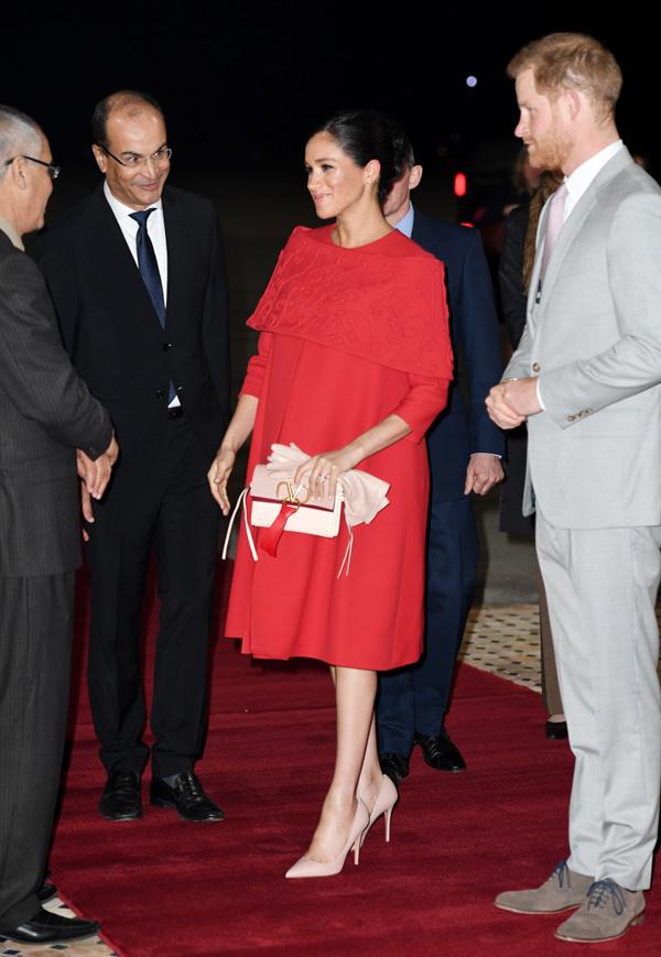 Tối chủ nhật, 23/2 Vợ chồng Harry - Meghan hạ cánh xuống sân bay ở Casablanca (Morocco), bắt đầu chuyến công du kéo dài 3 ngày tại quốc gia Bắc Phi. Nữ công tước xứ Sussex nổi bật trong  mẫu đầm cape đỏ của Valentino, kết hợp clutch cùng hãng. Không giống nhiều lần mặc đồ ôm sát trước đó, bà bầu hoàng gia chọn dáng  váy  rộng rãi, thoải mái cho cả mẹ và bé, tuy nhiên cô vẫn trung thành với giày cao gót - kiểu phụ kiện  không được khuyến khích với phụ nữ mang thai. Đầm Valentino: giảm giá còn 600 bảng.Clutch Valentino: 1.360 bảng.Khuyên tai Natalie Marie: 1.341 bảng.Giày Gianvito Rossi: 510 bảng.Găng tay Gianvito Rossi: 405 bảng.Tổng cộng set đồ: 4.216 bảng (129 triệu đồng).