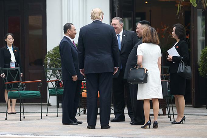 Kim Yo-jong (góc ngoài cùng bên trái) theo dõi cuộc trò chuyện giữa Tổng thống Donald Trump, Chủ tịch Kim Jong-un với các quan chức cao cấp trong khuôn viên khách sạn Metropole, Hà Nội, sáng 28/2. Ảnh: Reuters.