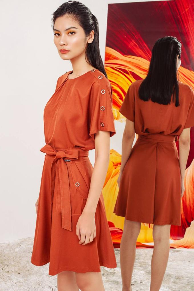 Một gợi ý đầm cam khác cho cô nàng điệu đà với điểm nhấn là nơ thắt lưng và chi tiết kim loại dọc cánh tay đơn giản, nhưng tạo điểm nhấn độc đáo.