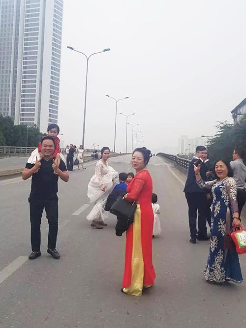 Cô dâu Thu Nga (váy trắng) và chú rể Quốc Huy (thứ 3 từ phải sang) đều vui vẻ dù bị cấm đường.