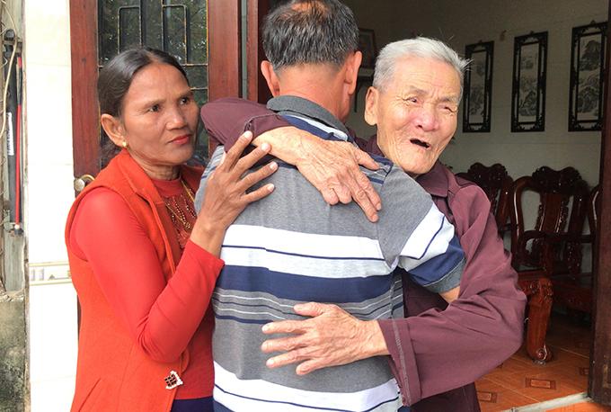 Ông Dương (giữa) ôm lấy cha già ngày trở về. Ảnh: Hùng Lê
