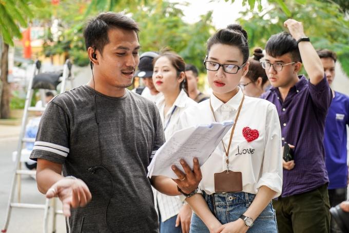Điều thú vị, nữ diễn viên vào vai một phóng viên giải trí và thực hiện phỏng vấn về cặp đôi Trường Giang - Nhã Phương trong video quảng cáo. Cô diện áo sơ mi, phối váy jeans và giày sneaker năng động.